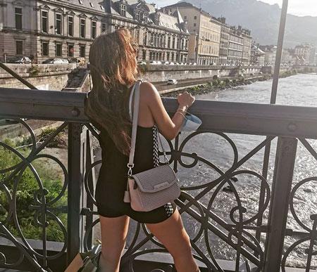 Die Casino Streamerin Tellia steht an einer Brücke am Flus und schaut verträumt in die Ferne