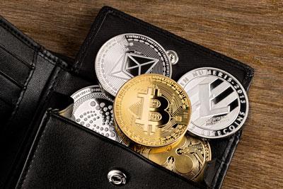 Eine Brieftasche mit Krypto Coins als Symbolbild für Krypto Wallets